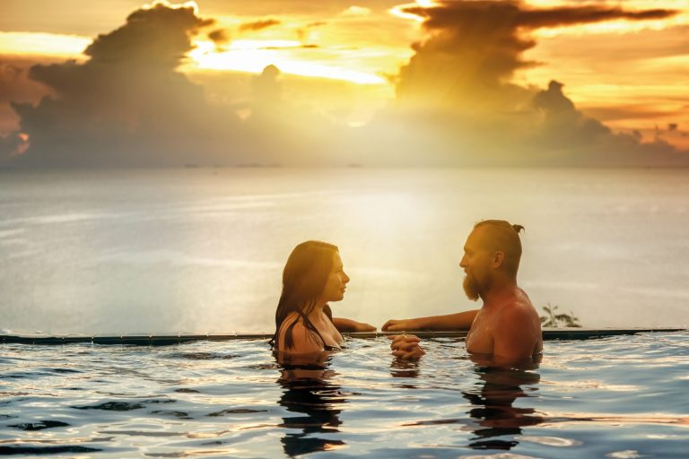 Romantic couple in the infinity pool at sunset overlooking the sea and sunset